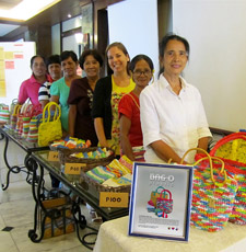 Peace Corps volunteer Rachael Saler, her counterpart (to her left) and women involved in the Bag-O Plastic group sell their products.