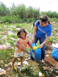 A young Filipino girl helps Peace Corps volunteer Rachael Saler collect plastic bags that will later be cleaned and crocheted into purses.