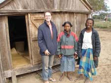Peace Corps volunteer Tatum Moorer in front of one of the schoolhouses with local community members.