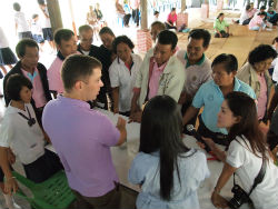 Peace Corps volunteer Roger Brubaker teaches people in his Thai community to make mosquito traps to reduce the incidence of Dengue fever.