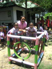 Peace Corps/Thailand volunteer Kathlyn Paananen at one of the playgrounds she helped her community build from donated motorcycle, car, and tractor tires.