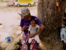 A Togolese mother feeds her baby enriched porridge