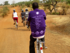 Peace Corps volunteers and counterparts bike along the way