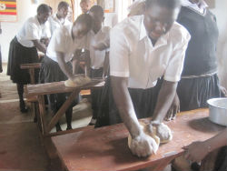 Students knead dough to prepare bread with Peace Corps volunteer Siong Ng