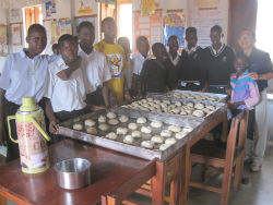 Peace Corps volunteer Siong Ng (right) teaches Ugandan students and teachers how to make bread.