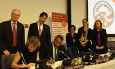 VSO Chief Executive Marg Mayne and Peace Corps Director Aaron S. Williams sign the agreement. Standing behind them from Left to Right: Sir Mark Lyall Grant, permanent representative of the United Kingdom to the United Nations, and Joseph M. Torsella, U.S. representative to the United Nations for Management and Reform, and staff.