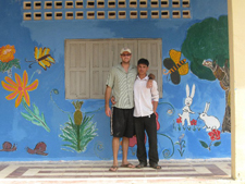 Peace Corps volunteer Ryan Young and a Cambodian friend in front of the renovated resource center.