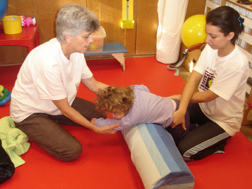 Christine (left) demonstrates proper handling techniques for relaxing stiff muscles in a child with cerebral palsy.