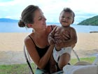 Lauren Goodwin, a Peace Corps Response Volunteer in Malawi, holds a friend's baby at Mangochi beach.