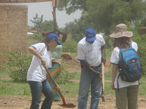 Stephanie Servetz, a Peace Corps Response Volunteer in Burkina Faso, planted trees at a construction site with community members and other Peace Corps Volunteers.