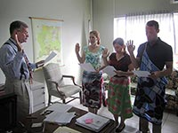 Peace Corps Response Volunteers (from left) Karin Jones, Sarah Tourville and Eddy Gastel are sworn into service by former Country Director George Like.