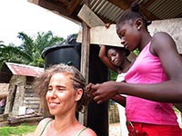 Peace Corps Response Volunteer Alan Feldman Soler gets her hair braided by children in the Saramaacan community of Gran Tatai.