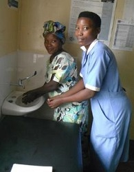 Two healthcare workers wash their hands
