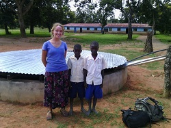 Peace Corps volunteer Deirdre Clarke stands primary school children in front of the school's water catchment system