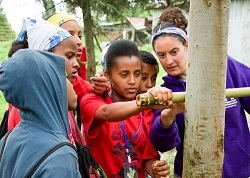 PCV Lauren Mazza and campers measure tree with bamboo Biltmore Stick