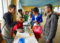 Students teach community members about science experiments at the community fair