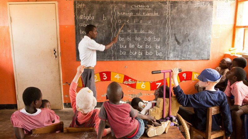 A teacher in Malawi teaches young children in a small classroom