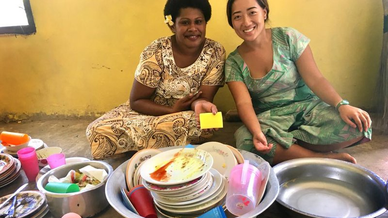 Asian Pacific American Volunteer sits with Fijian woman washing dishes