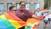 A man with a Native background wraps a rainbow flag around himself and a friend, smiling.