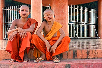 Two young monks sitting together chatting
