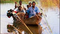 Villagers and their bikes are ferried across the Bandama River on a pirogue (canoe).