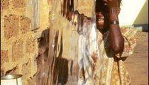 Nombara, 15, pours water from her basin into a large metal drum where her family stores water for cooking and washing.