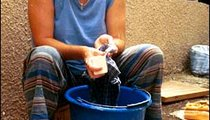 Peace Corps Volunteer Natalie Kusmerski is hand-washing her laundry out in the courtyard.