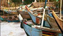 On Sunday, their only day of leisure, fishermen dock their boats on the beach in the crowded fishing port.