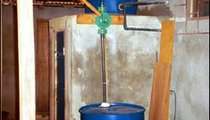 This is a gravity-flow water system. The bottom barrel is filled with water from the well, then hand-pumped into the top barrel, which is positioned above the indoor sink, enabling the family to have running water.