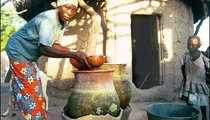 Madago uses a calabash to retrieve water from her cannerie. The hand-made canneries keep water cool in the heat of the day.