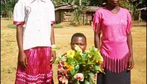 Bevette, Stasia, and Nilia display the flowers they picked in the village for the school inspector, who will visit today. Flowers grow more abundantly during the long rainy season, from October to December.