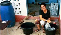 As a Peace Corps Volunteer, I am washing clothes by hand using two buckets, each half full of water. One bucket is for lathering and the other is used for rinsing. My water comes from a water storage tank situated on top of a concrete tower.