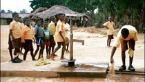 A boy sweeps off the borehole at the school compound. This is one of the daily chores for the children. The yellow-and-brown uniforms are worn by children throughout Ghana.