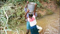 A boy helps a young girl lift her bucket. Water is heavy, and generally the containers are so big, it is impossible to lift them alone.