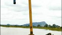 A water pump on Lake Volta pulls water from the lake and will shoot it through the overhanging nozzle into trucks. The trucks take the water and wash the roads of dirt and debris during harmattan (the windy season) or they haul it to construction sites.