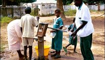 Students and a teacher are pumping water for drinking. The school pump is used many times a day to fetch water for drinking, washing, and cooking.