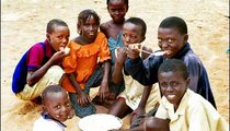 These students are eating dugola, a corn-based porridge made with water, sugar, and corn, prepared by the school cooks for the daily lunch.