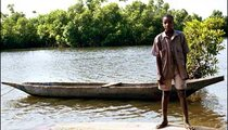 Ibrimah Dico stands on top of an overturned canoe in the River Gambia, which is a source of fish, crabs, and clams for the Gambian people.