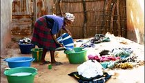 Binta Jallow pours water into her wash bucket, as she prepares to tackle the piles of clothes before her.