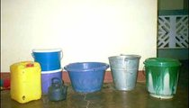 "These are the six different water containers I use in my daily life: the green bucket holds drinking water, the metal bucket is used for well water, the purple one is my wash basin, the teapot is for hand-washing, there is a two-bucket filter system, and the yellow jug is for ""clean"" pump water."