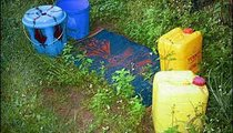 This is where I shower. The two buckets are for water storage. The two bidons (the yellow containers) are used for hauling water. The abundance of plant growth indicates that it is the rainy season.