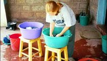 """I'm washing clothes, using one bucket for lathering and one for two """"rinse cycles."""" We wash clothes about once every two weeks to conserve water. The water is very dirty, but we use it until it almost looks black before changing it."""