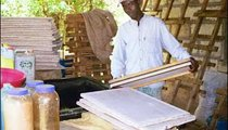 A man makes paper from local sedges, a fibrous plant. The fibers are immersed in a basin of water and soda and then are dried on trays. There is a growing market for homemade paper. It is simple to make and all materials are found locally.