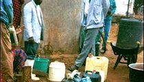 The hospital's concrete water tank is filled by a lorry (truck) from the next town once or twice a month. It is the hospital's only water tank and is vital to its functioning. These men, relatives of patients, have lined up to ask for water.