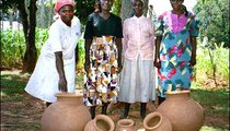 One Maragoli art form that still thrives in Kenya is that of making clay pots, which are used to carry and store water. Here are (left to right) Grace Msimbi, Erica Kahega, Nifreda Mbone, and Jessica Nangai, the makers of the pots. The small pots in front are for flowers.