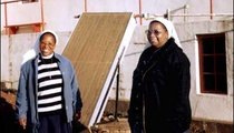 Sister Mary Louisa and Sister Mary David, sisters of the Sacred Heart, help run the local clinic at Christ the King Mission. They are standing in front of a solar-powered water heater used for the clinic patients. The mother superior of the convent controls the water supply, which is pumped from the spring and flows through pipes to the mission.