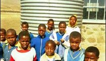 Children stand in front of the water tank that collects rainwater for the Ha Sekhohola Primary School. It remains empty most of the year.