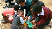 "Students of Makoanyane Primary School are washing their bowls before lunch. This is the only kind of ""play"" that students have with water."