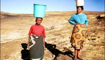 These women walked down a mountain to get water from a stream. Now, with the water in the buckets on their heads, they have to go back up to get to their homes.