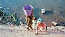 A girl carries water from the Niger River. Water is always carried in a bucket balanced on the head. Carrying water is a job performed by women and children.